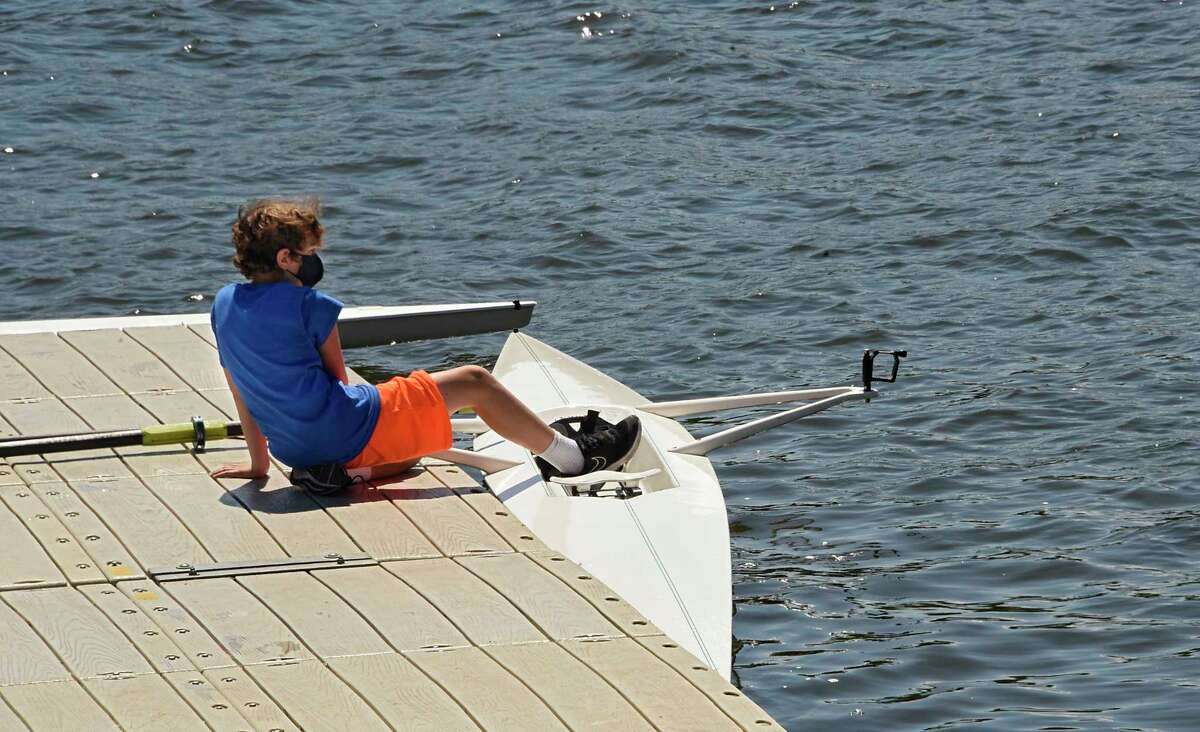 Chaz Siegfeld, 12, of Albany sits on a dock at the Corning Preserve boat launch after rowing on the Hudson River with the Albany Rowing Club on Friday, July 31, 2020 in Albany, N.Y. (Lori Van Buren/Times Union)