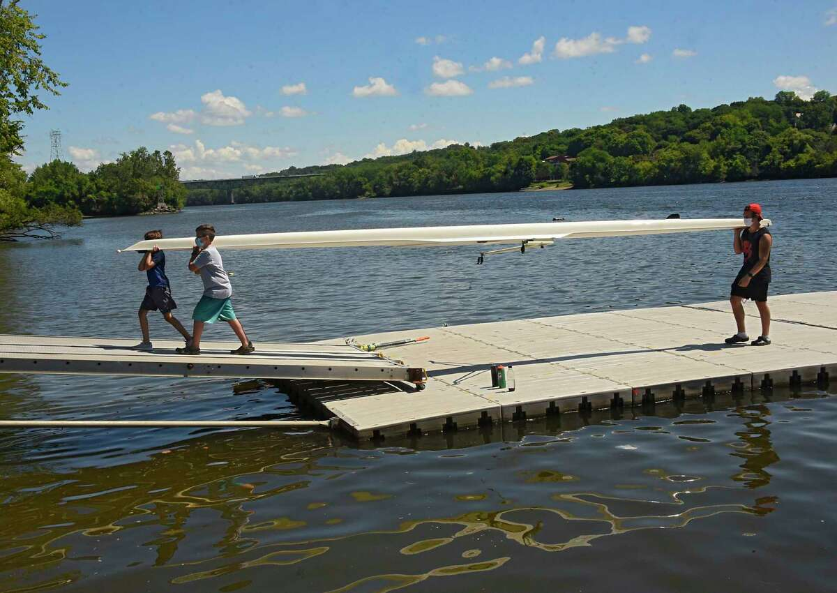 From left, Ethan Filippelli of Loudonville, Ben Gable of Delmar and Bill Gannon of Albany carry a rowing shell over a dock at the Corning Preserve boat launch and back into the storage shed after rowing with the Albany Rowing Club on Friday, July 31, 2020 in Albany, N.Y. (Lori Van Buren/Times Union)
