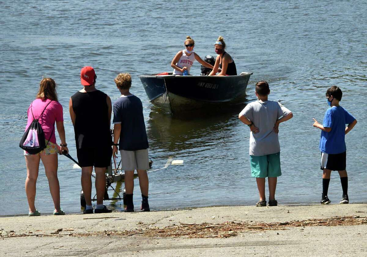 People guide a boat onto a carrier after a rowing session on the Hudson River with the Albany Rowing Club on Friday, July 31, 2020 in Albany, N.Y. (Lori Van Buren/Times Union)