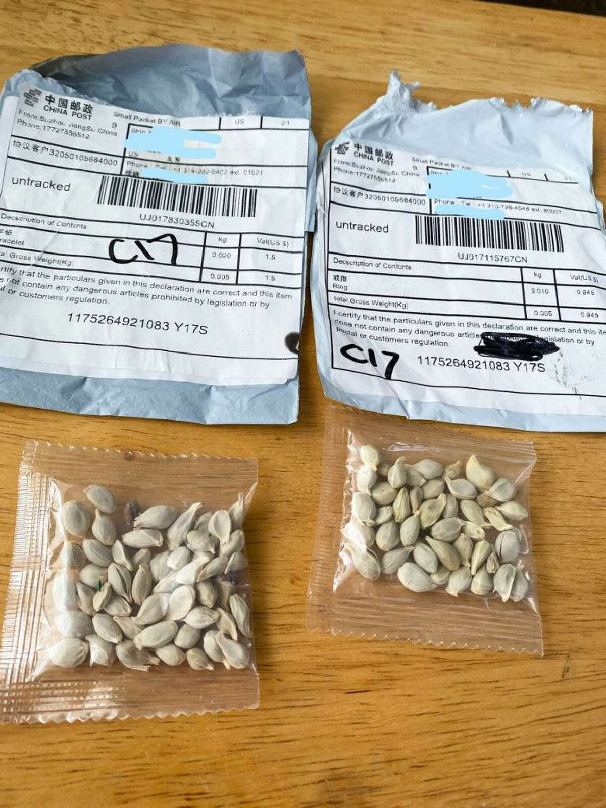 These packages sent from China contain unidentified packets of seeds with Chinese text printed on them. The small packages often arrive in the mail with labels indicating the contents are jewelry or other small items, but when the recipient opens the package, they find packets of seeds instead. The danger is that the unknown seeds could pose a threat to the agriculture industry.
