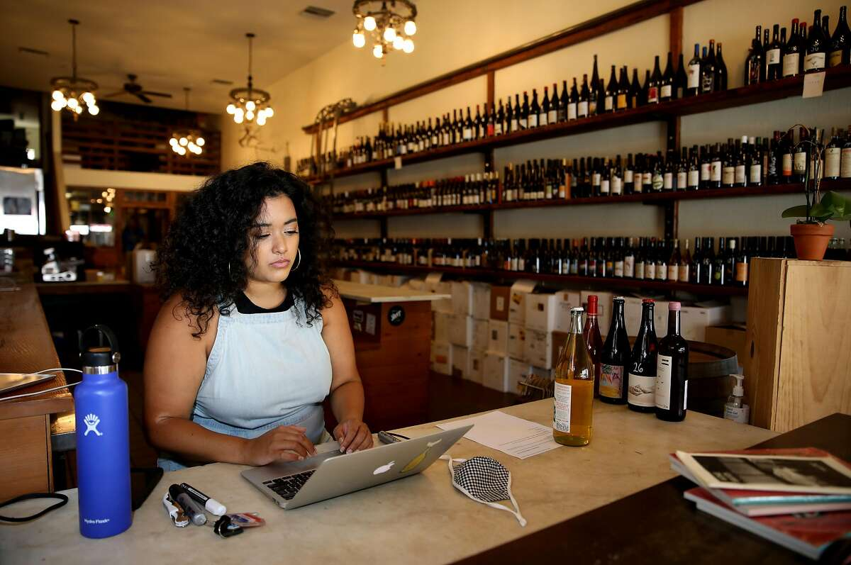 Jirka Jireh, a manager and sommelier, works on an order at Ordinaire Wine Shop and Wine Bar, located at 3354 Grand Ave., on Friday, July 10, 2020, in Oakland, Calif. Jireh has begun organizing virtual wine classes for BIPOC across the country; the classes are free for all students, with the instructor donating time and wine companies donating all the wine.