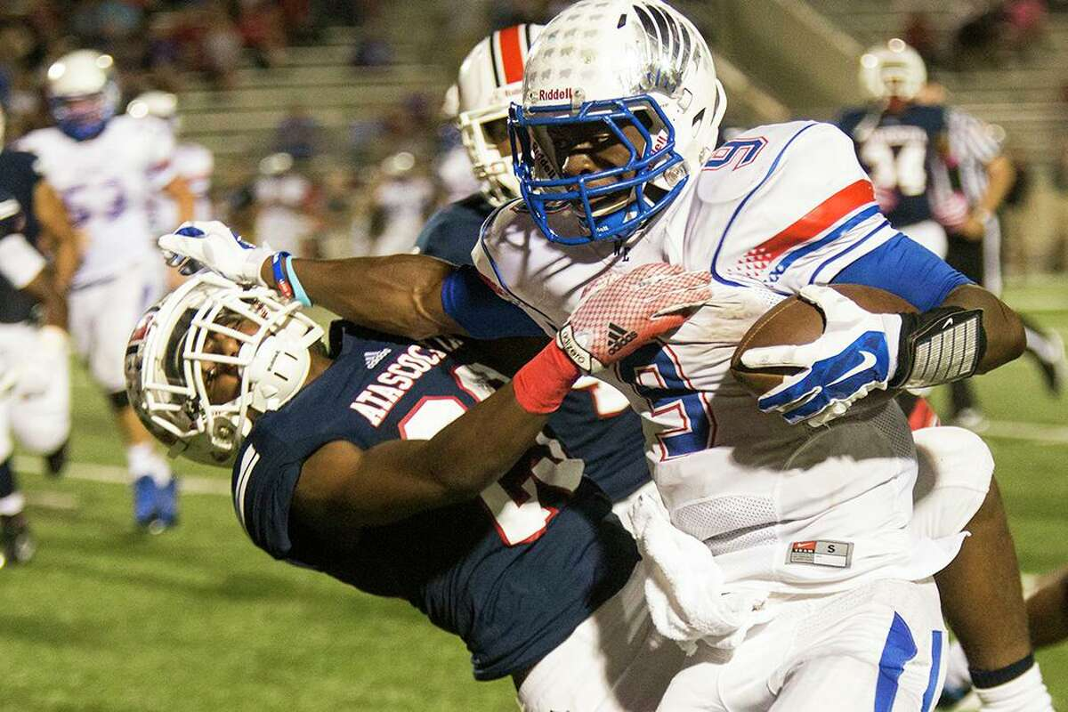 War Eagles running back Kwame Etwi (9) stiff arms a defender during Atascocita's 49-27 victory over Oak Ridge on Oct. 10, 2014, at Turner Stadium in Humble.