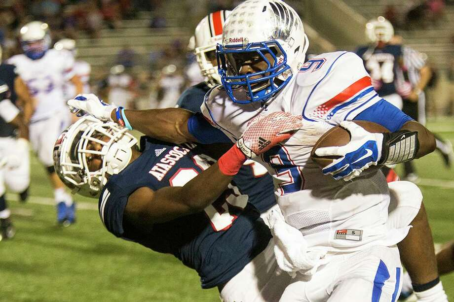 War Eagles running back Kwame Etwi (9) stiff arms a defender during Atascocita's 49-27 victory over Oak Ridge on Oct. 10, 2014, at Turner Stadium in Humble. Photo: ANDREW BUCKLEY / Internal