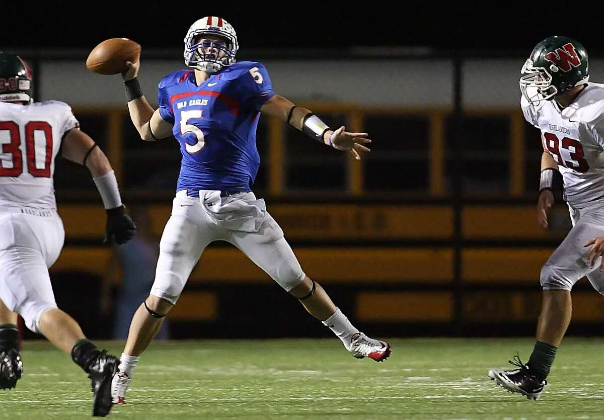 Oak Ridge quarterback Chris Grett comes under pressure from The Woodlands defenders as he looks for an open man during Thursday night's game at Woodforest Stadium in Shenandoah. To purchase this photo or others like it, visit: http://hcnonline.mycapture.com