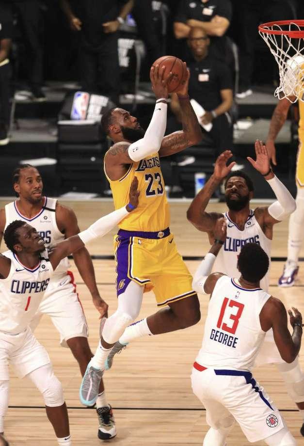 LeBron James (en el centro) anota la canasta decisiva en el triunfo de los Lakers sobre los Clippers el jueves 30 de julio en Lake Buena Vista, Florida. Previamente se arrodilló para escuchar el himno nacional junto al resto de los equipos antes del partido de la NBA. Photo: AP