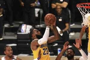 LeBron James (en el centro) anota la canasta decisiva en el triunfo de los Lakers sobre los Clippers el jueves 30 de julio en Lake Buena Vista, Florida. Previamente se arrodilló para escuchar el himno nacional junto al resto de los equipos antes del partido de la NBA.