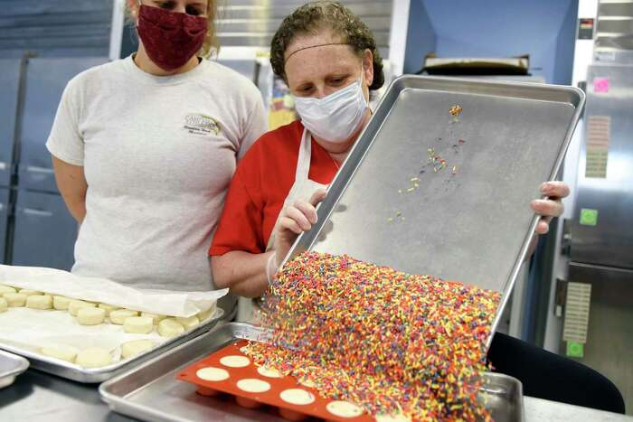 Julie Tolkin and her daughter, Corey, dump a tray of spinkles on top of a batch of cookie dough bites at the Unbakeables kitchen in Norwalk, Conn. Wednesday, July 29, 2020. Unbakeables recently received a $10,000 state loan to help them stay afloat during the coronavirus pandemic and were visited by Conn. Lt. Gov. Susan Bysiewicz earlier this week to see how the loan has helped them.