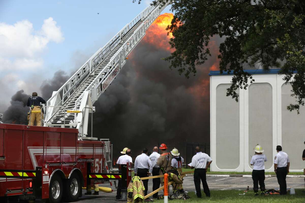 Firefighters battle a fire near the intersection of Westpark Drive and Fairhill Drive on Friday, July 31, 2020, in Houston.