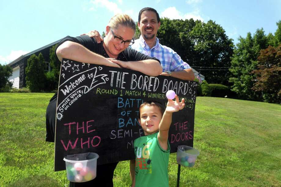 "Jaimee and Brian Solomon pose next to their ""Bored Board"" with their son, Peter, in front of their Trumbull, Conn. home July 29, 2020. Photo: Ned Gerard / Hearst Connecticut Media / Connecticut Post"