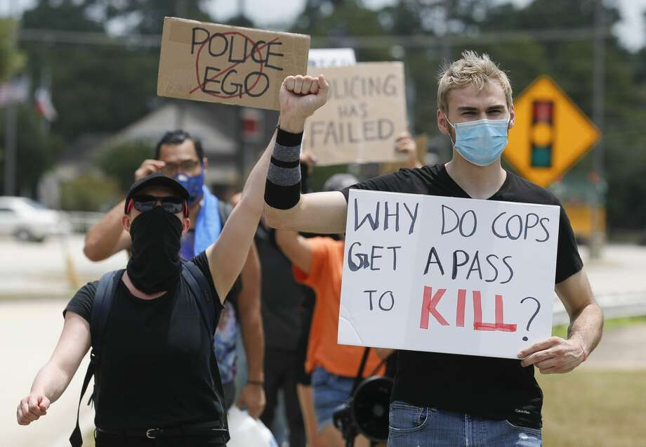 Antonella Diaz, right, helps lead a group of protesters hold signs and chant as they cross North Loop 336 toward the Conroe Police Department to march against the 2013 death of 19-year-old Russell Rios, Friday, July 31, 2019, in Conroe. Conroe Police Sgt. Jason Blackwelder was off duty when he shot Rios, a suspected shoplifter, as he fled from a Walmart store into the woods nearby. Blackwelder was found guilty of manslaughter, but was sentenced to five years probation. Photo: Jason Fochtman/Staff Photographer / 2020 © Houston Chronicle