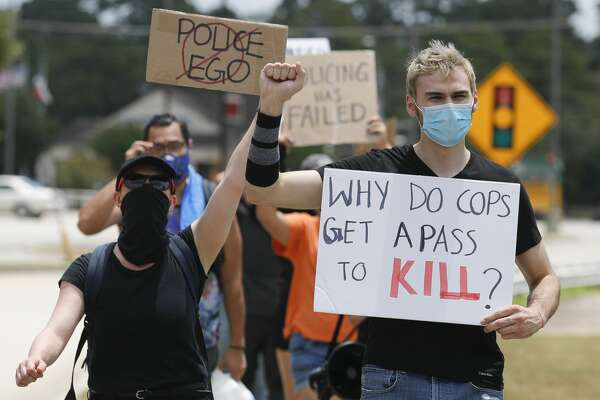 Antonella Diaz, right, helps lead a group of protesters hold signs and chant as they cross North Loop 336 toward the Conroe Police Department to march against the 2013 death of 19-year-old Russell Rios, Friday, July 31, 2019, in Conroe. Conroe Police Sgt. Jason Blackwelder was off duty when he shot Rios, a suspected shoplifter, as he fled from a Walmart store into the woods nearby. Blackwelder was found guilty of manslaughter, but was sentenced to five years probation.