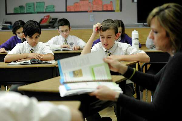 In 2017, sixth-graders, from left, Georen Chirayil, Aidan Saraiva and Thomas Cunningham study religion with teacher Deanna George class at St. Joseph School in Danbury. After being closed for months because of the pandemic, the Bridgeport Diocese is preparing to open Catholic schools in the diocese.