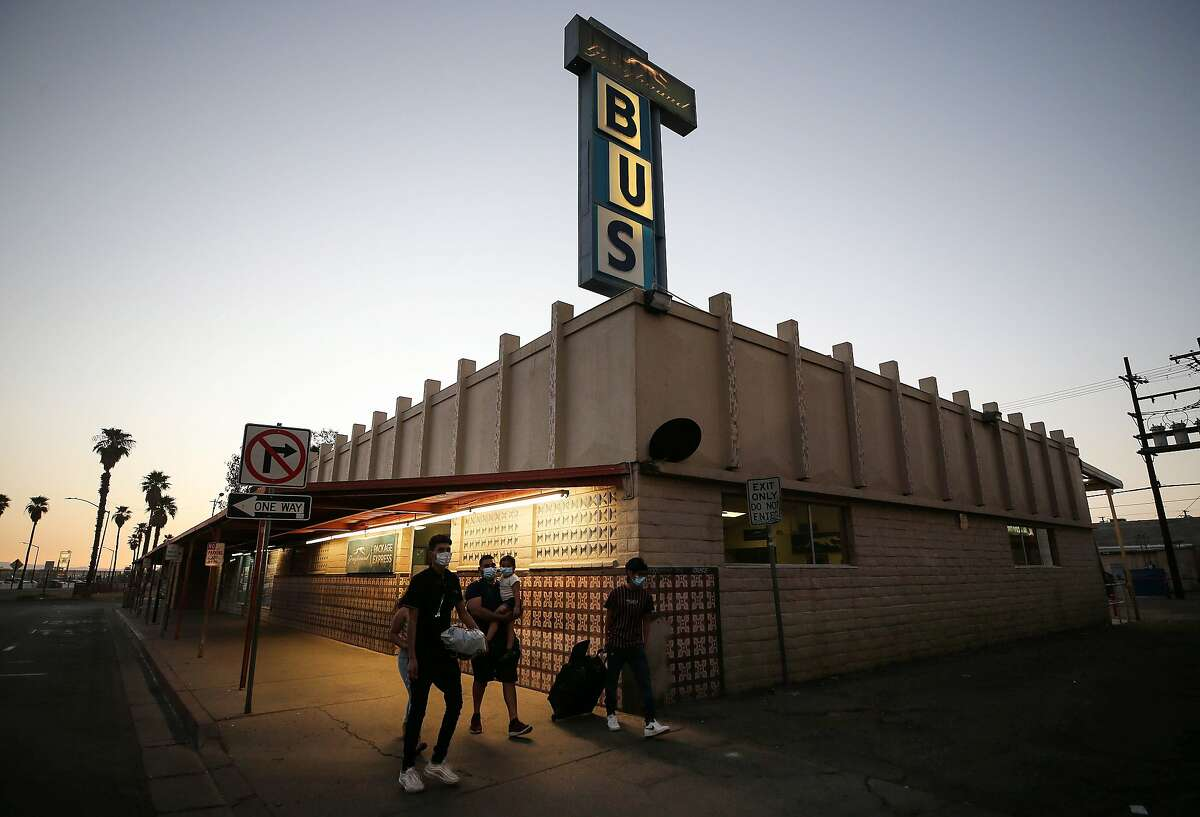 CALEXICO, CALIFORNIA - JULY 22: People wear face masks as they walk past a shuttered Greyhound bus station near the U.S.-Mexico border in hard-hit Imperial County amid the COVID-19 pandemic on July 22, 2020 in Calexico, California. Imperial County current