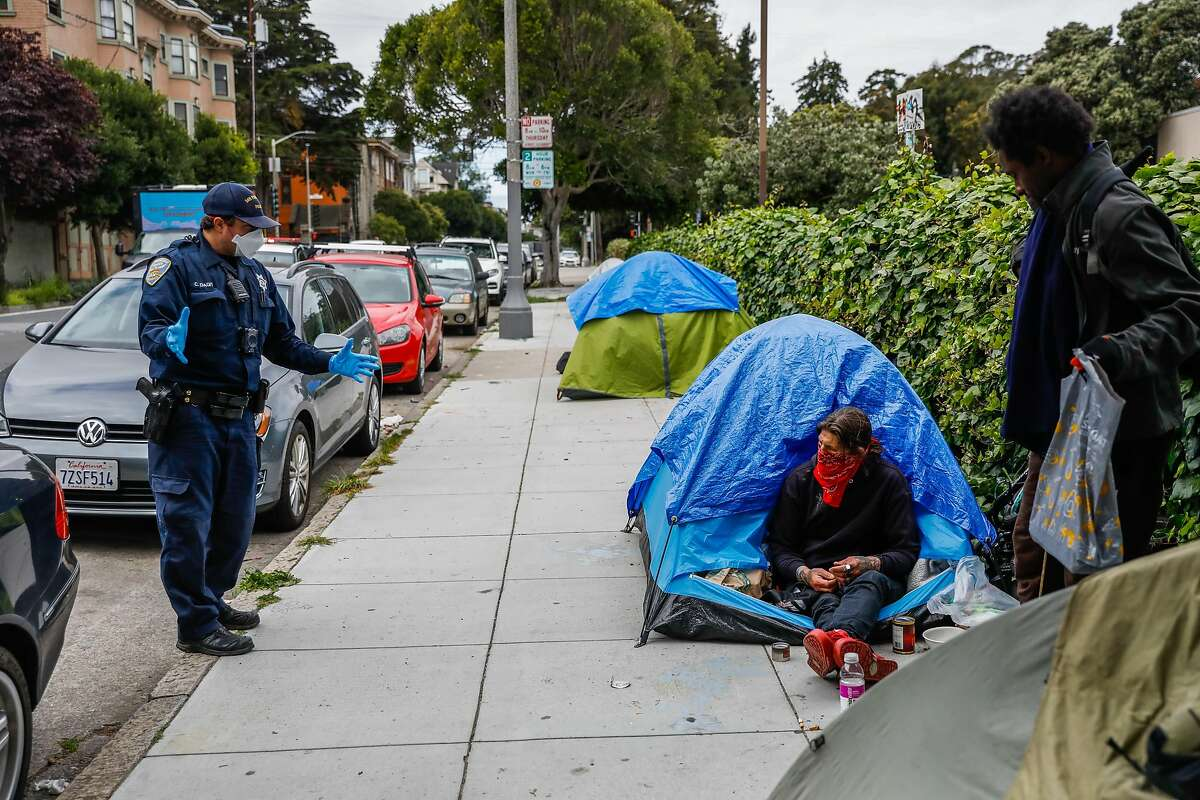 A police officer asks homeless men to socially distance from one another outside a tent encampment on Oak Street in San Francisco, where at least 8,000 are believed to be homeless.