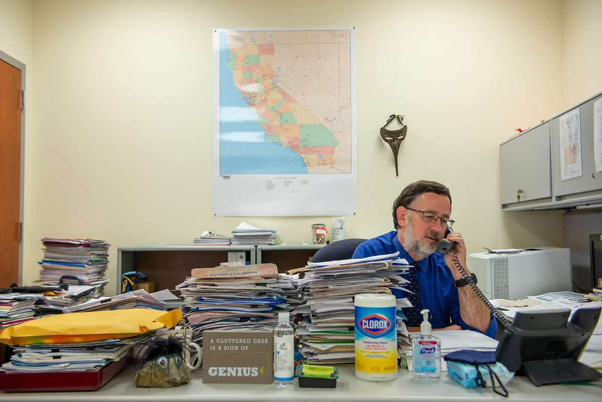 Dr. Bela Matyas, who conducted a case investigation telling public health officials that social gatherings are responsible for more than 95% of all recent cases, takes a phone call in his office on July 24, 2020 in Fairfield, Calif.