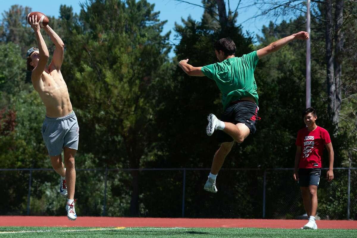 Charlie Craig, Campolinda High School Senior, 17 years old, catches a football during a Lamorinda Bomb Squad practice at Campolinda High School Stadium while practicing with Zack Raphael, 17 yr. old senior, and Josh Tsai, 14 yr. old freshman, on July 31, 2020 in Moraga, Calif.