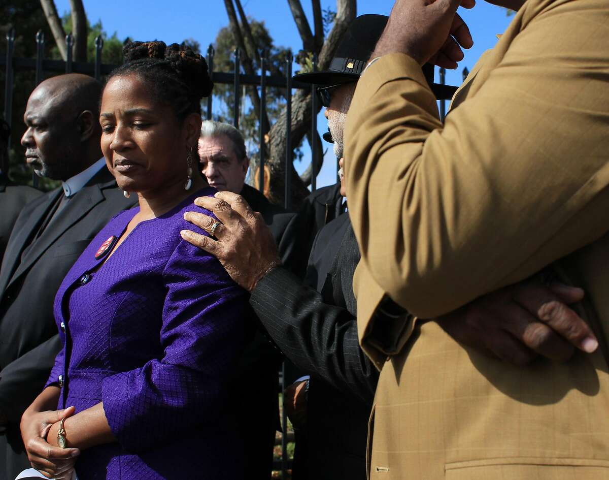 Lynette McElhaney gets a pat on the shoulder by Melin Edwards of the African American Chamber of Commerce as members of the Oakland Clergy gather at the corner of 7th and Market to endorse McElhaney for Oakland City Council, Tuesday Oct. 30, 2012, in Oakland, Calif.