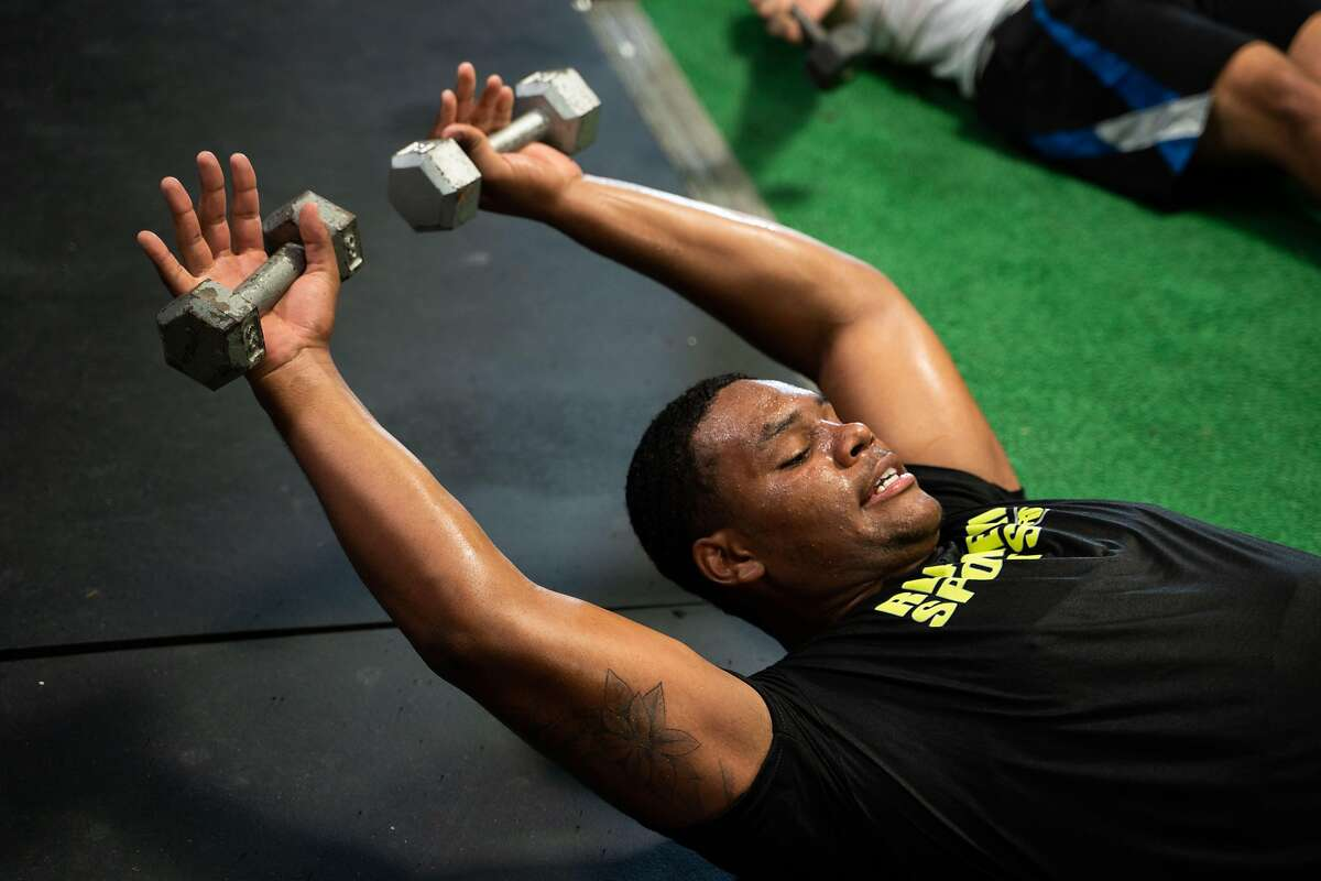 Akili Calhoun, 18, of Brentwood, lifts dumbbells during an ab workout circuit at Tenacity Training Center in Antioch, Calif., on Monday, July 27, 2020.