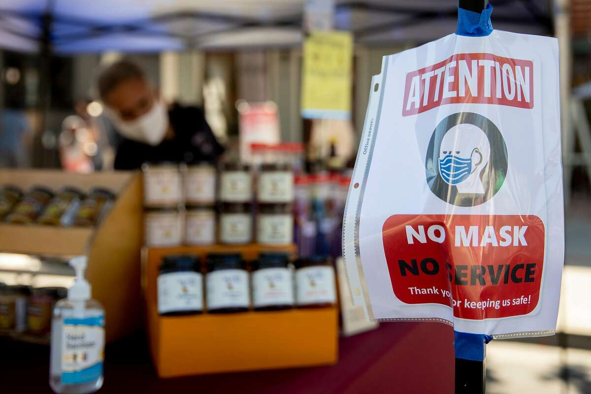 """A sign alerting customers to the statewide mask mandate is posted at the Benicia Farmer's Market in Solano County on Thursday, July 30, 2020. Solano could move backward to California's most restrictive """"widespread"""" purple reopening tier after hovering on the edge for several weeks."""