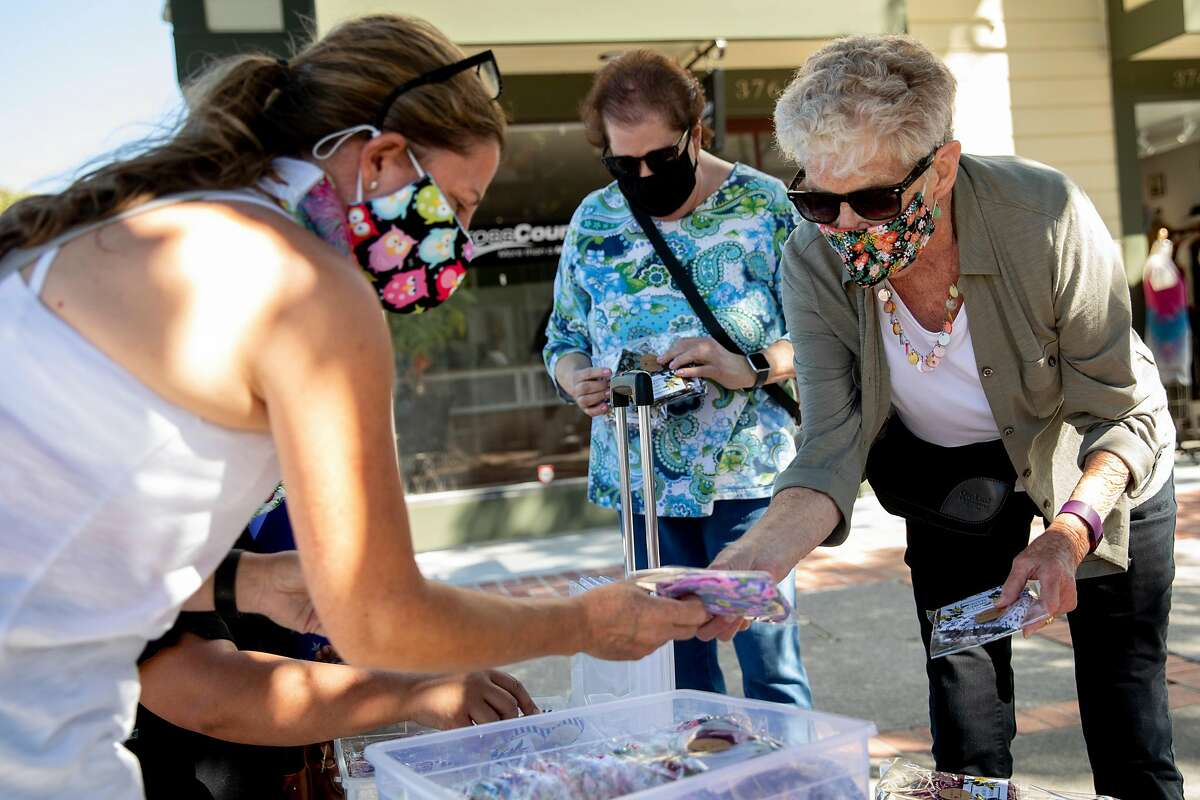 Juliana Fabbri (left) of My Mom's Masks sells a mask to Benicia resident Jeanne Brown (right) outside of the Benicia Farmer's Market in Benicia, Calif. Thursday, July 30, 2020. The Head of Solano County says 95% of cases over the past two weeks in Solano County have been from social gatherings. Public health officials say they have this information from contact tracing, but they rarely share it. Epidemiologists and infectious disease experts say they need to understand how the virus spreads in the community to help develop strategies to fight it.