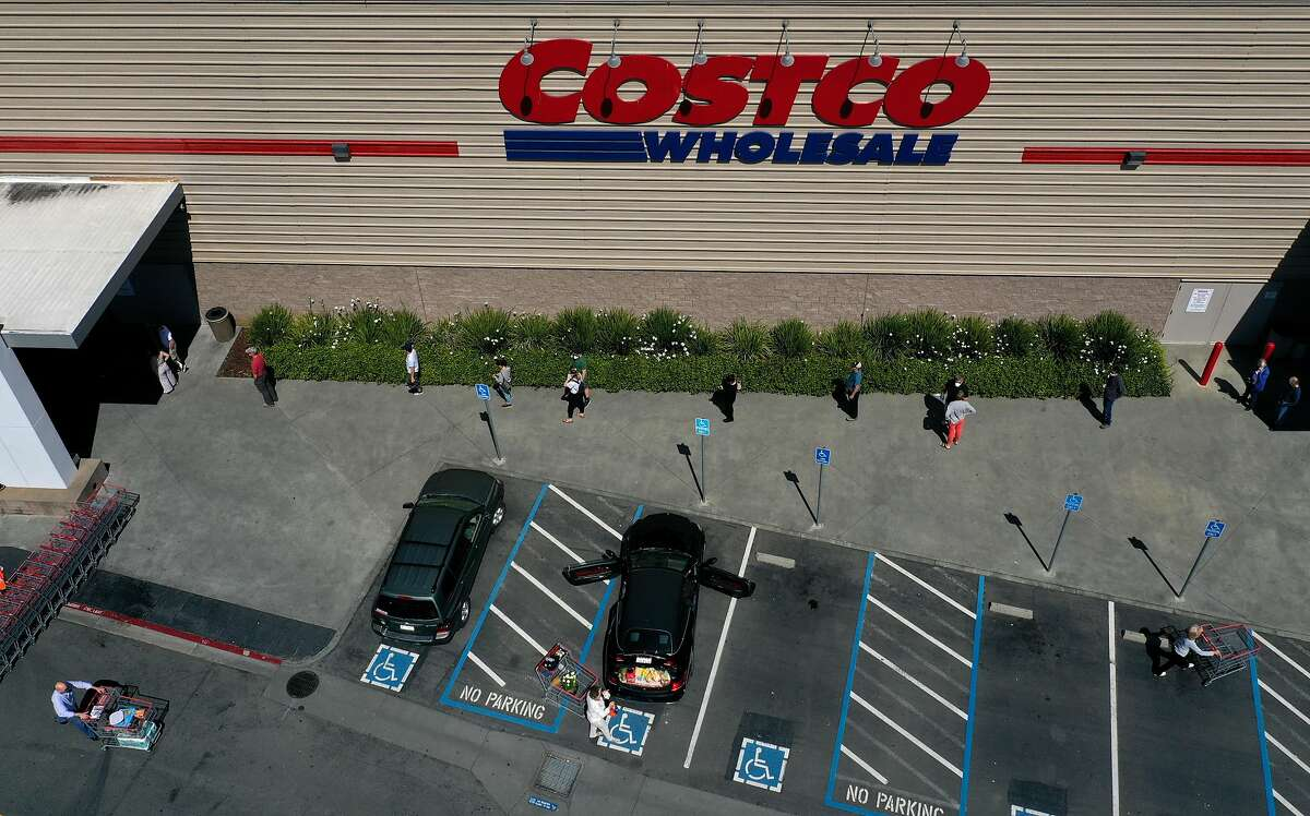 In this aerial view from a drone, shoppers practice social distancing waiting in line to enter a Costco store on April 13, 2020 in Novato, California. California is projected to reach a peak in COVID-19 deaths on Wednesday