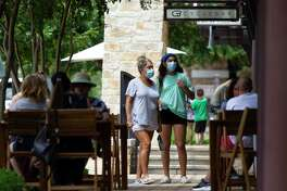 Women wear face masks as they shop at Creekside Park Village Green, Wednesday, July 29, 2020, in The Woodlands.