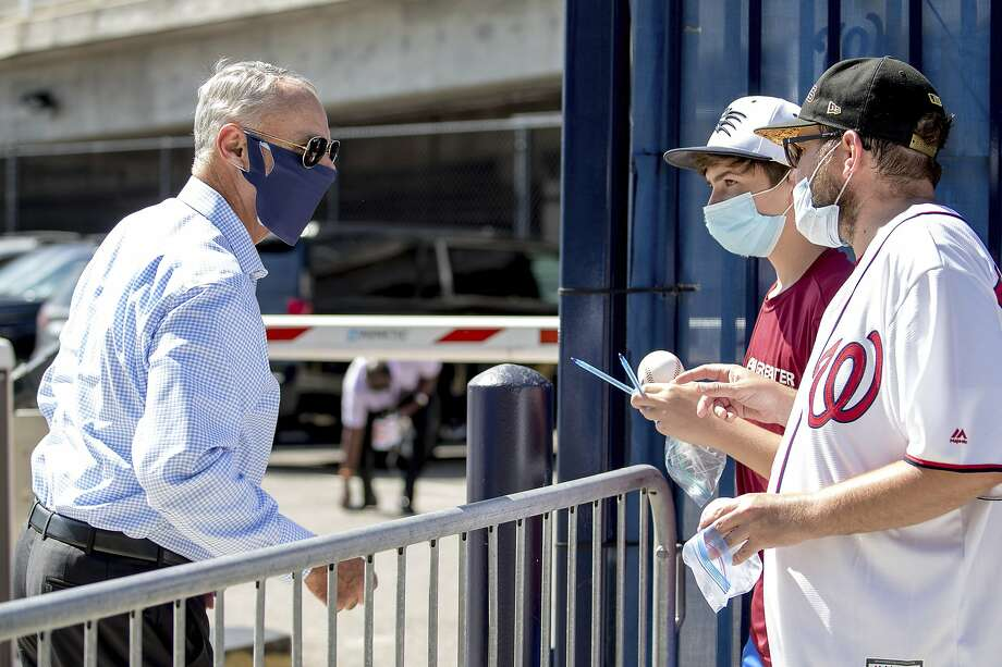 MLB Commissioner Rob Manfred (left) speaks with fans in Washington on July 23. With 20% of MLB teams sidelined because of positive coronavirus tests, Manfred reportedly is considering shutting down the season. Photo: Andrew Harnik / Associated Press