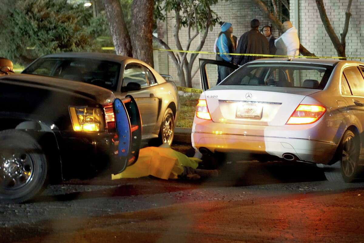 36-year-old Antronie Scott's body lays under a tarp next to his car Thursday night, Feb. 4, in the parking lot of the Wood Hollows Apartments, 10362 Sahara Street. Scott was shot by San Antonio Police officer John Lee, an 11-year veteran, who was attempting to arrest him on two felony warrants.