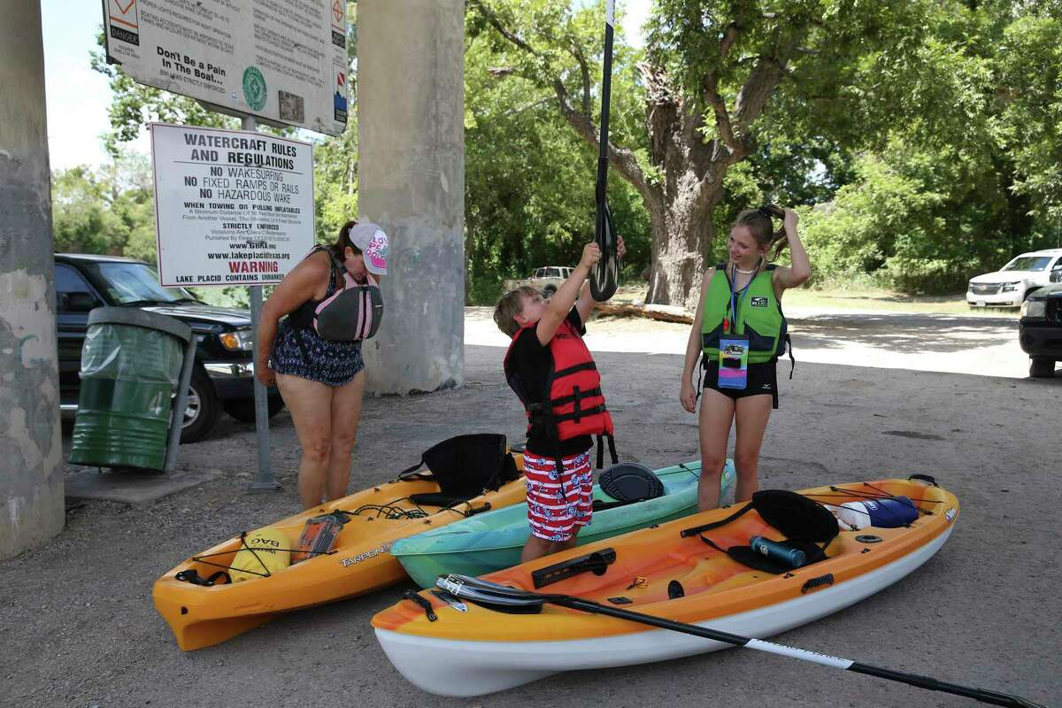 From left, Llan Allen, 59, Korbin Hall, 8, and Brianna Allen, 12, prepare for kayaking at Lake Placid near Seguin, Texas, Sunday, Aug. 11, 2019. After the collapse of the Lake Dunlap dam on May 14, the Guadalupe-Blanco River Authority is planning on draining the remaining four dams for safety inspections.