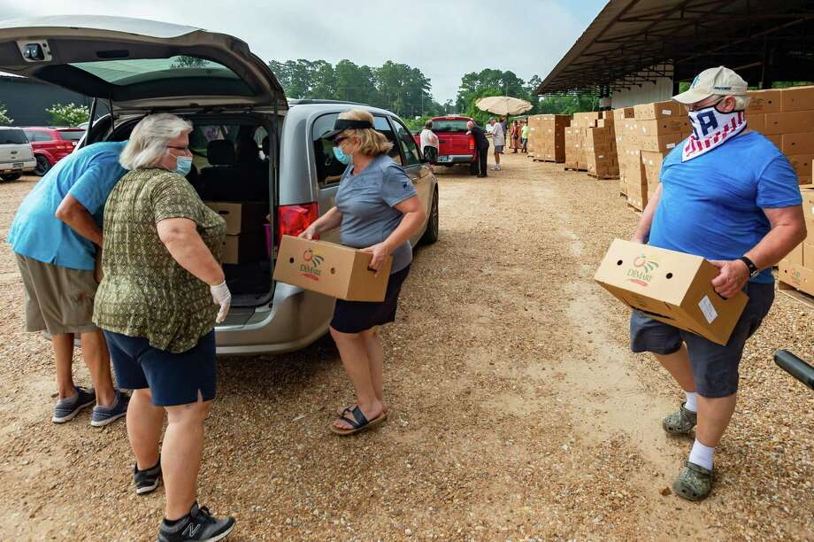 Volunteers at Harvest Church in Jasper load Farm to Family food boxes into a line of vehicles on Friday morning. Some were picking up several boxes and delivering them to family and neighbors who are also low on food. After several of Jasper County's food banks closed at the start of the coronavirus back in April, all five are up and running again. The demand still remains high and the Southeast Texas Food Bank is hoping the supply of produce increases.. Photo made on July 10, 2020. Fran Ruchalski/The Enterprise Photo: Fran Ruchalski, The Enterprise / The Enterprise / © 2020 The Beaumont Enterprise