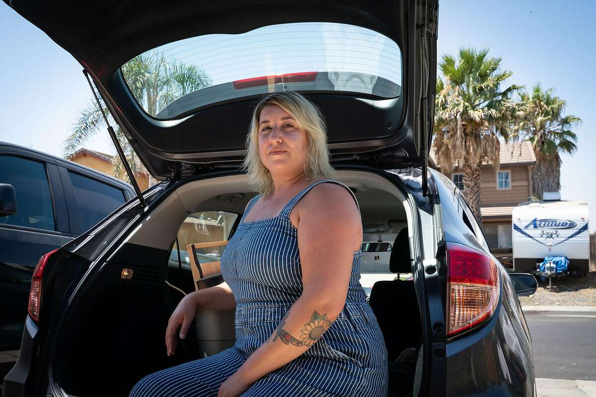 Kristina Lancaster, 31, poses for a photo after arriving at her brother's home in Brentwood, Calif., on Monday, July 27, 2020. After losing work as a hair stylist due to the coronavirus pandemic, it took four months until Lancaster received any of her unemployment benefits. Lancaster plans to stay with family and friends in Brentwood, San Francisco and Oregon over the coming months.