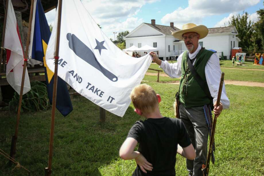 "John Meredith, of The Sons of the Republic of Texas, explains the history behind the ""Come and Take It"" flag from the Battle of Gonzales to James Nicas, 8, during the Texian Heritage Festival on Saturday, Oct. 7 2017, at Fernland Historical Park in Montgomery. Photo: Michael Minasi, Staff Photographer / Houston Chronicle / © 2017 Houston Chronicle"