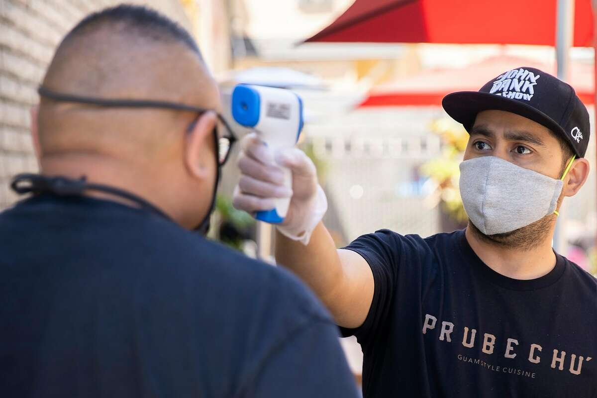 Prubechu co-owner Shawn Camacho checks the temperature of a customer before letting him into the outdoor seating area on July 30, 2020, in San Francisco.