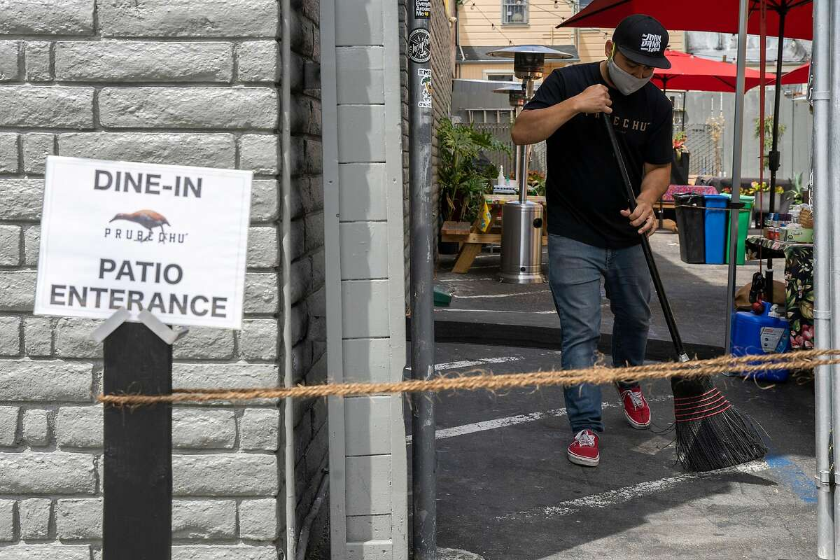 Prubechu co-owner Shawn Camacho sweeps the area before opening the food business to customers on Thursday, July 30, 2020, in San Francisco, Calif.