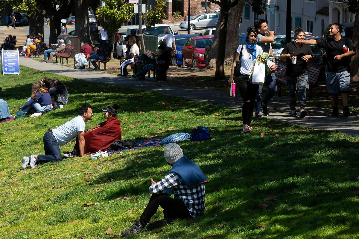 A group of people walk along the sidewalk without their masks on as they find a spot at Dolores Park on Tuesday, July 28, 2020, in San Francisco, Calif.