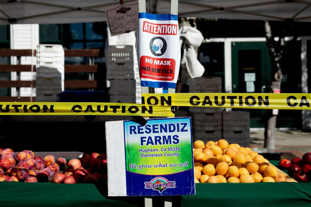 Caution tape surrounds produce while signs inform patrons of the statewide mask mandate at the Benicia Farmer's Market in Benicia, Calif. Thursday, July 30, 2020. The Head of Solano County says 95% of cases over the past two weeks in Solano County have been from social gatherings. Public health officials say they have this information from contact tracing, but they rarely share it. Epidemiologists and infectious disease experts say they need to understand how the virus spreads in the community to help develop strategies to fight it.