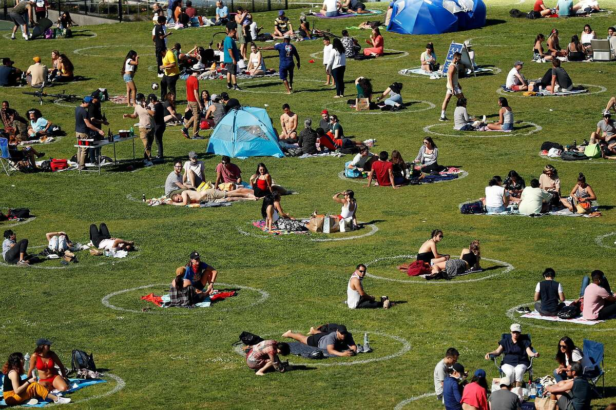 People socialize in the social distancing circles at Mission Dolores Park in San Francisco, Calif., on Sunday, May 24, 2020.