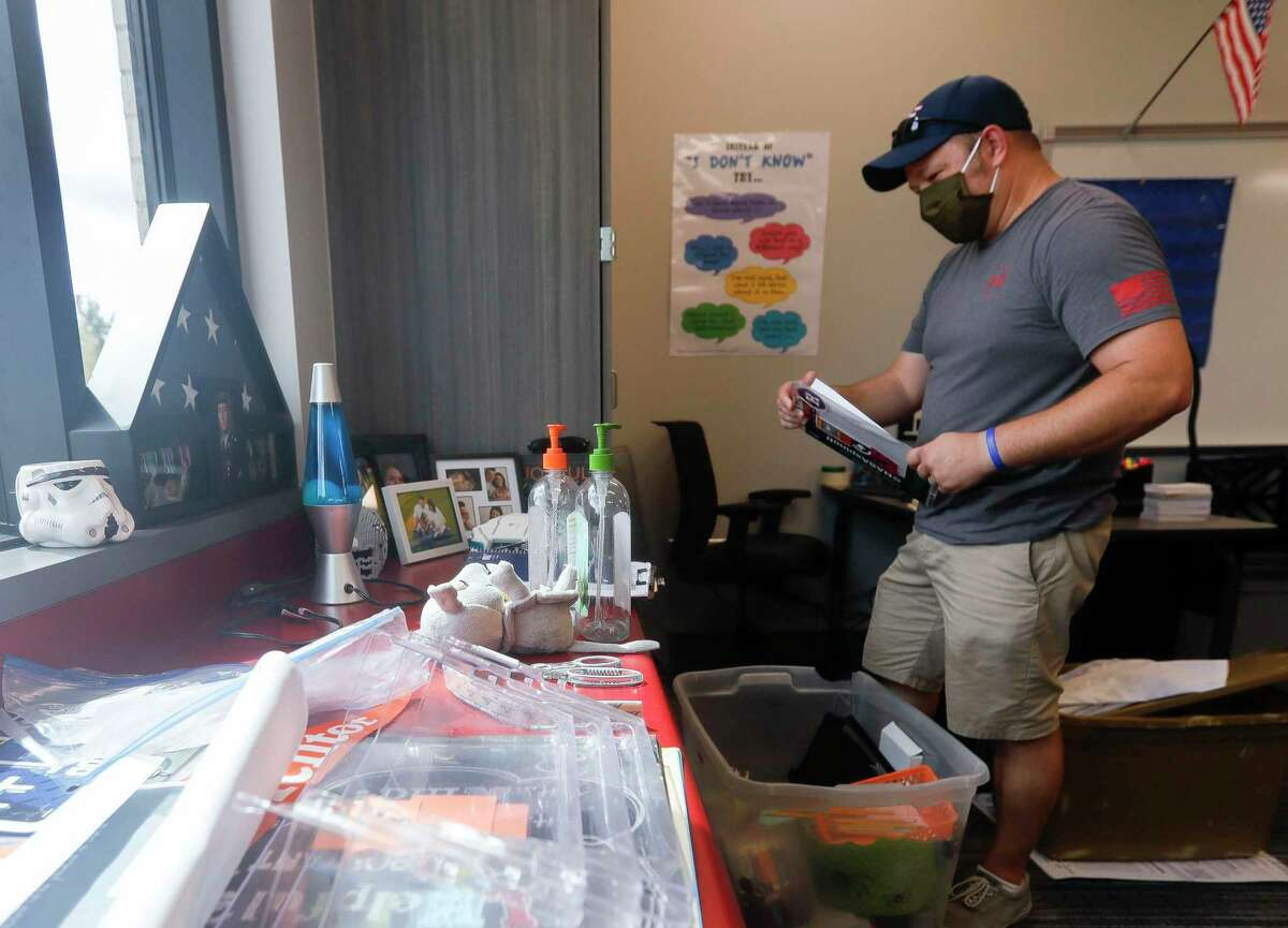 Seventh grade history teacher Robert Simard unpacks items for his classroom despite not starting the school year with students in the space at the new Donald J. Stockton Junior High School, Wednesday, July 29, 2020, in Conroe.
