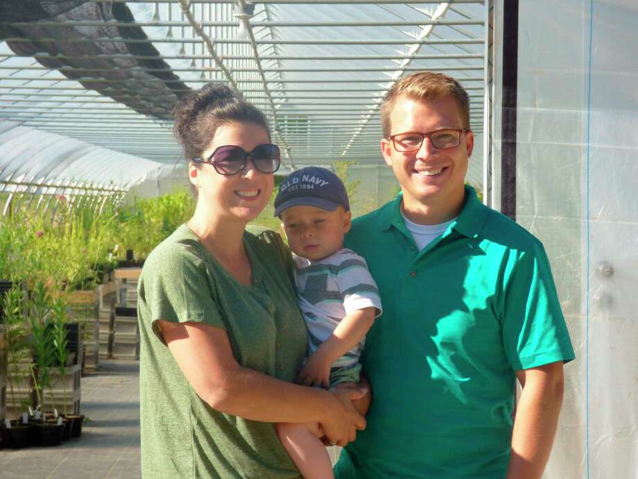Jennifer and Matt LaMore, co-owners of Black Cap Farm, pose with their son Henry in front of their greenhouse which recently opened in Onekama. (Scott Fraley/News Advocate)