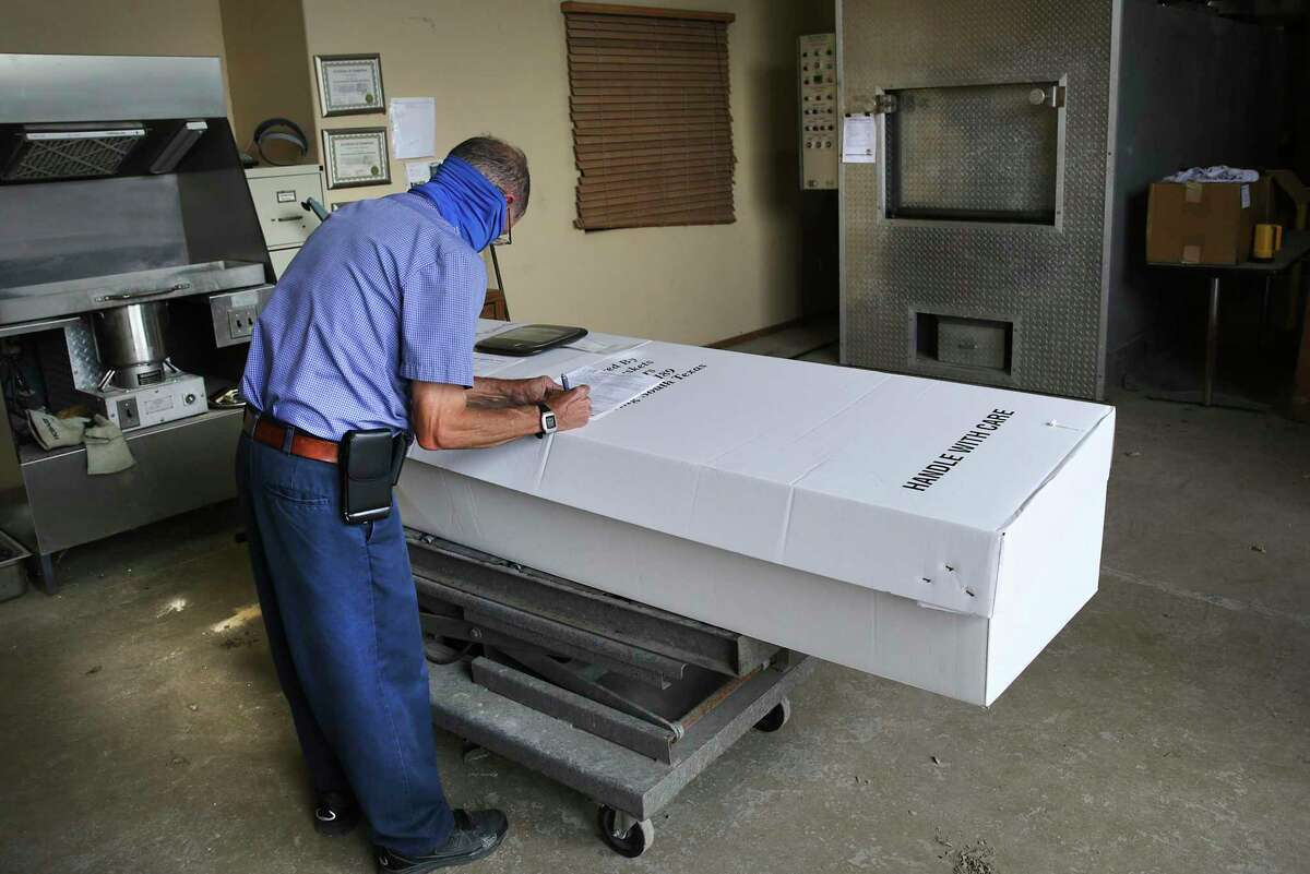 Sam Olivarez, a co-owner of Garden of Angels cemetery in Mission, prepares a body for cremation.