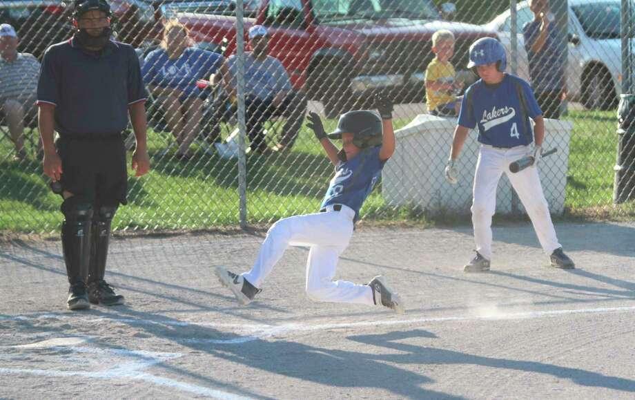 Laker shortstop Calvin Edmondson slides into home at Sands Park on Friday. (Kyle Kotecki/News Advocate)