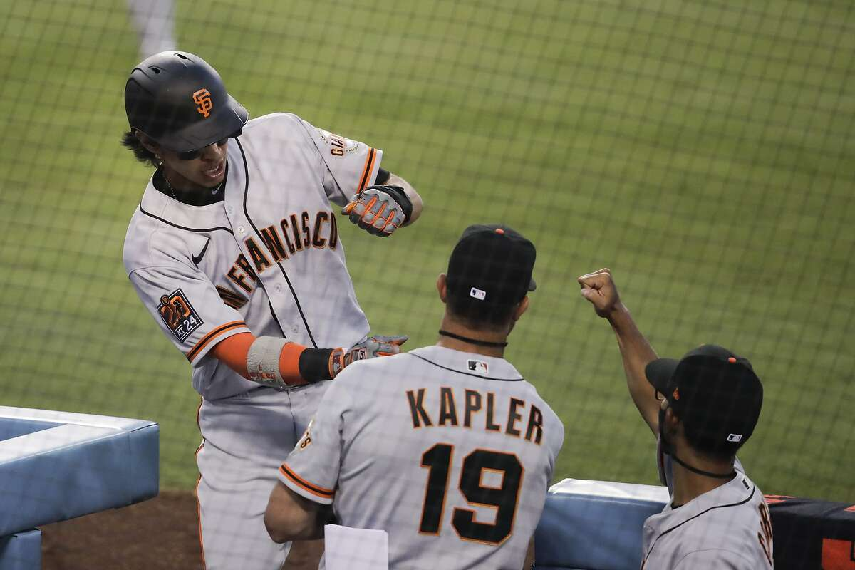 San Francisco Giants' Mauricio Dubon, left, is greeted by manager Gabe Kapler, center, and bench coach Kai Correa after scoring on a single by Darin Ruf during the third inning of the team's baseball game against the Los Angeles Dodgers, Sunday, July 26, 2020, in Los Angeles. (AP Photo/Jae C. Hong)