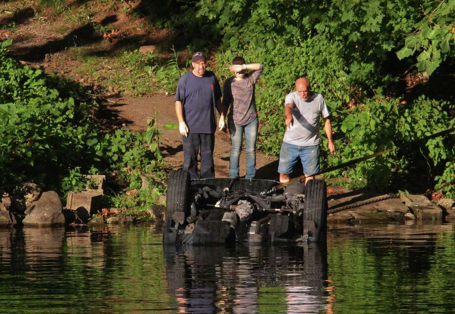 Officials investigate after a vehicle landed in the Housatonic River in Seymour, Conn., on Friday July 31, 2020. First responders rushed to the area of 179 Roosevelt Drive (Route 34) shortly before 4 p.m. after a crash on the side of the road catapulted a vehicle into the Housatonic River, according to initial dispatch reports. Photo: Christian Abraham / Hearst Connecticut Media / Connecticut Post