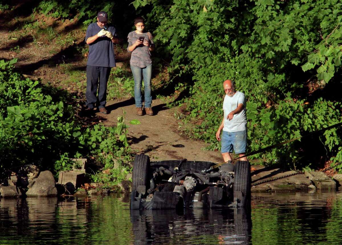 Officials investigate after a vehicle landed in the Housatonic River in Seymour, Conn., on Friday July 31, 2020. First responders rushed to the area of 179 Roosevelt Drive (Route 34) shortly before 4 p.m. after a crash on the side of the road catapulted a vehicle into the Housatonic River, according to initial dispatch reports.