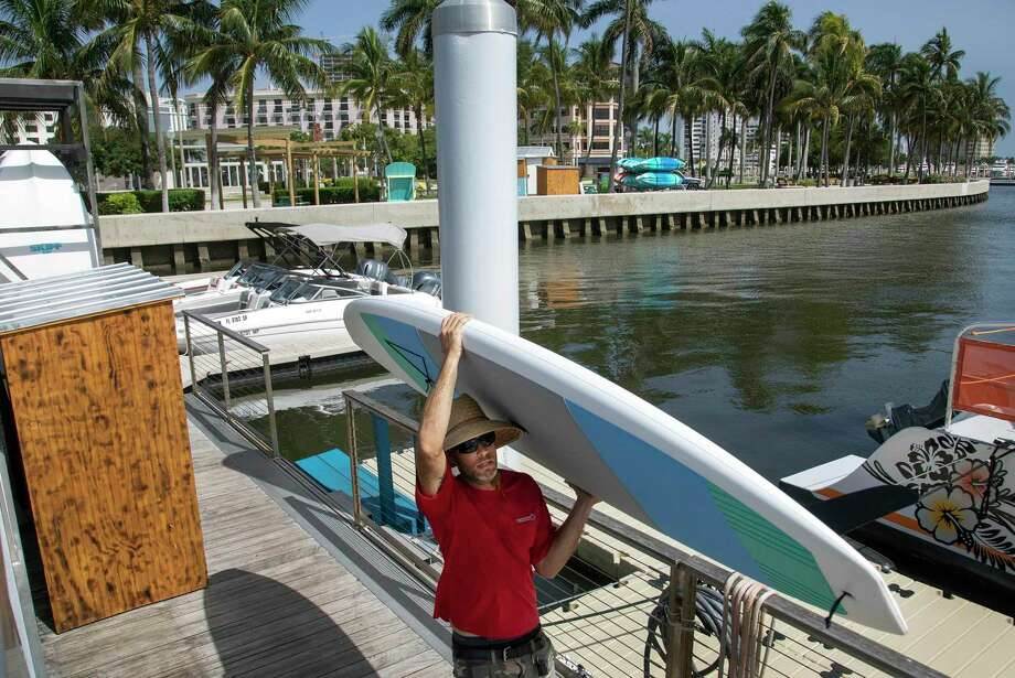 Erin Flaherty removes paddle-boards from the city docks, Friday, July 31, 2020, in West Palm Beach, Fla., in advance of Hurricane Isaias. Forecasters have declared a hurricane watch for parts of the Florida coastline as Hurricane Isaias drenches the Bahamas on a track for the U.S. East Coast. (Lannis Waters/The Palm Beach Post via AP) Photo: Lannis Waters / THE PALM BEACH POST