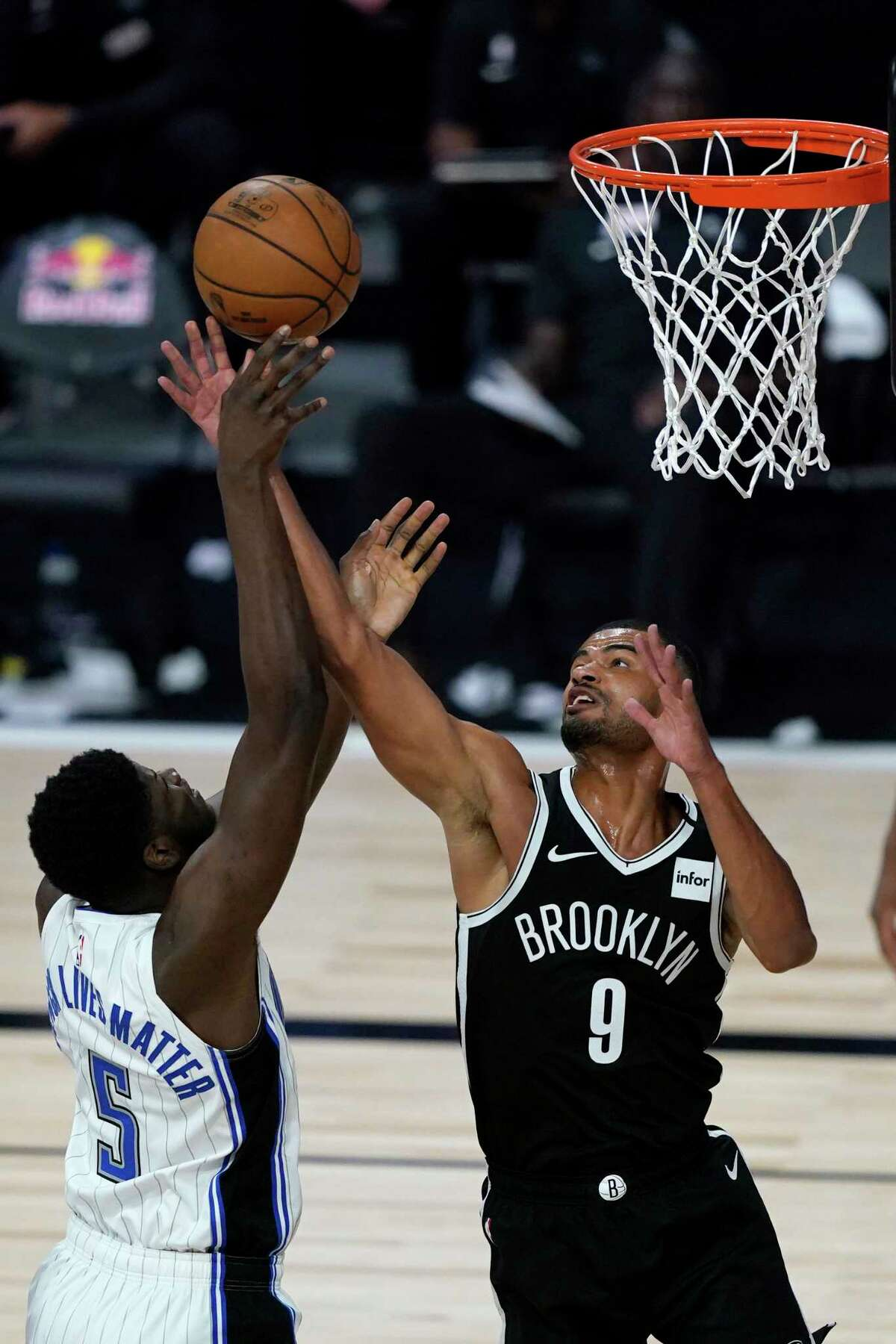 Brooklyn Nets' Timothe Luwawu-Cabarrot (9) and Orlando Magic's Mo Bamba (5) reach for a rebound during the second half of an NBA basketball game Friday, July 31, 2020, in Lake Buena Vista, Fla. (AP Photo/Ashley Landis, Pool)
