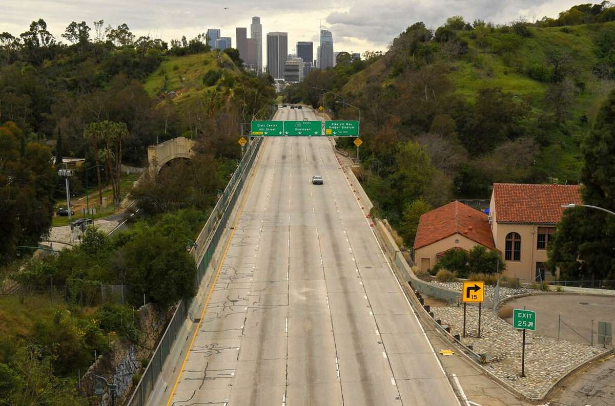 Extremely light traffic moves along the 110 Harbor Freeway toward downtown Los Angeles on a Friday in March. Traffic would normally be bumper to bumper during this time of day, but the shelter-in-place is keeping residents home.
