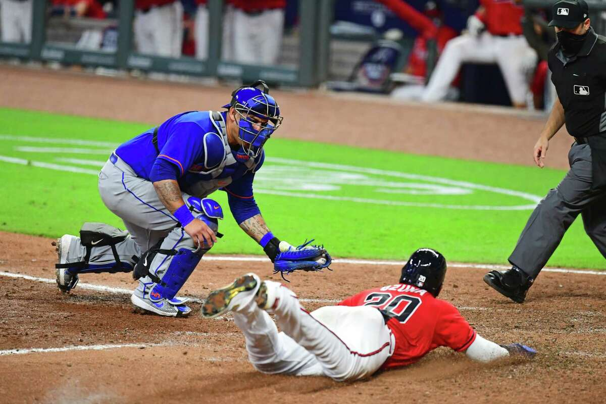 ATLANTA, GA. - JULY 31: Marcell Ozuna #20 of the Atlanta Braves slides home safely in the eighth inning against Wilson Ramos #40 of the New York Mets at SunTrust Field on June 31, 2020 in Atlanta, Georgia. (Photo by Scott Cunningham/Getty Images)