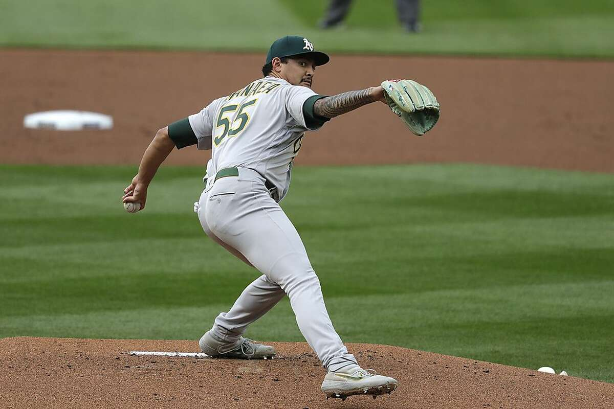 Oakland Athletics starting pitcher Sean Manaea throws against the Seattle Mariners in the first inning of a baseball game during the Mariners home opener Friday, July 31, 2020, in Seattle. (AP Photo/Elaine Thompson)