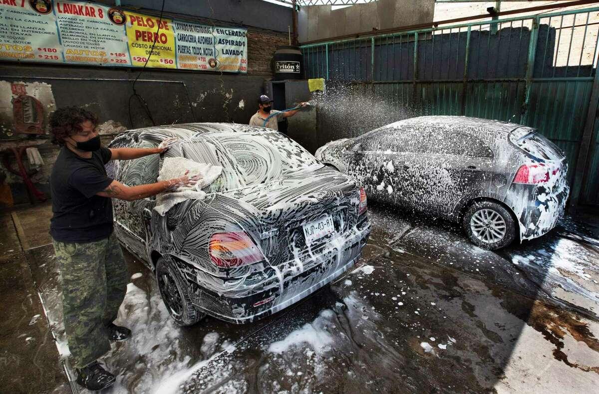 """?""""scar Aguilera y Juan Martínez lavan automóviles el viernes 31 de julio de 2020 en el autolavado Lavakar, en la Ciudad de México. Ambos portan mascarillas para protegerse del coronavirus."""